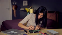 Cute woman trying to fix hard disk at home Stock Footage