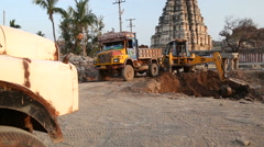 Digger slowly digging dirt in front of temple Virupaksha. Stock Footage