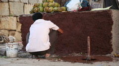 Man pargeting with dirt on the street of Hampi. Stock Footage
