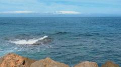 Serene Blue Sea, Waves Breaking Into Rocks Stock Footage