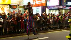 The clown on stilts at the parade passes by spectators Stock Footage