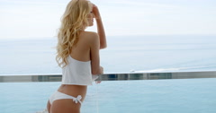 Blond woman wearing white bikini and silky top Stock Footage