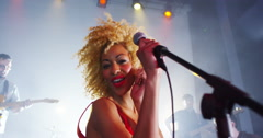 Stock Video Footage of 4K Beautiful charismatic female singer performing with band at live music event