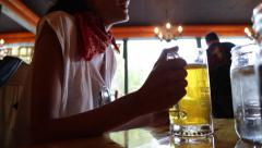 Happy Woman Drinks Beer and Checks Smartphone Stock Video - stock footage