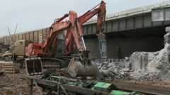Back hoe collects shattered concrete pieces at construction site Stock Footage