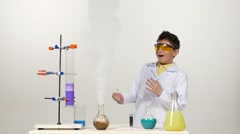 Little boy chemist in uniform, protective glasses Stock Footage