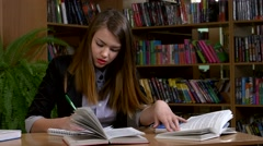 Stock Video Footage of Portrait of clever student with open book reading it in college library