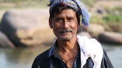 Elderly indian man looking at the camera on the Tungabhadra river. Stock Footage
