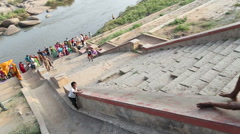 Children using hand-hold as a slide on the riverside in Hampi. - stock footage