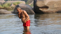 Stock Video Footage of Indian man standing in the river and taking bath.