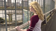 Girl Day Dreams Of Adventure, Looks Out Over Free Way, City In Background (4K) Stock Footage