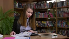 Stock Video Footage of Portrait of clever student with open book reading it in college library, slow