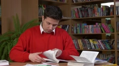 Student researching with a book in a library, slow motion Stock Footage