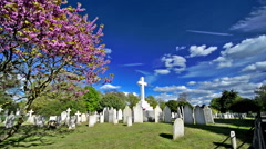 Brompton cemetery, London. White cross with clouds and blue sky Stock Footage