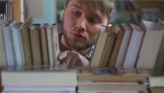 Stock Video Footage of Young man browsing through the racks of books in a library