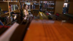 A portrait of girl student reading a book in the library, slow motion Stock Footage