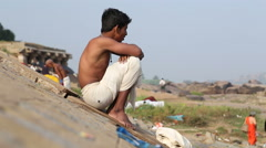 Young boy in white shorts sitting on the riverbank. Stock Footage