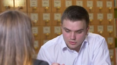 young man with other bookshelves in background - stock footage