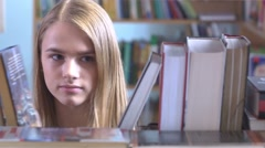 Pretty young girl chooses a book in the library Stock Footage