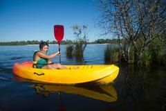 Teen making canoe kayak on a lake Kuvituskuvat