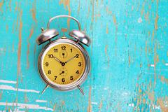 Vintage Retro Alarm Clock on Rustic Blue Background Stock Photos