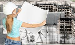 Young woman in white hard hat holding paper Stock Photos
