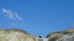 Couple standing and talking on the top of sandy dune hill under beautiful clean Stock Footage