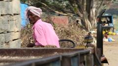 Man in pink shirt slowly driving backwards little traktor. - stock footage