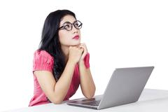 Pensive woman with laptop imagine something - stock photo