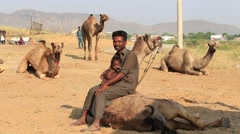 Poor man with a child sitting on a camel in Pushkar Camel Mela. India Stock Footage
