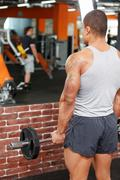 Back view of weightlifter in gym - stock photo