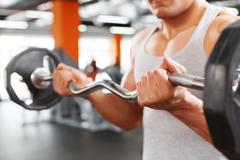 Close up of weightlifter with barbell - stock photo
