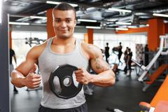 Weightlifter holding disk with thumbs up - stock photo