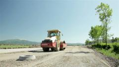 Road compactor leveling gravel, preparing base for new asphalt at the highway. Stock Footage