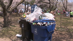 Overflowing garbage trash and recycling bins in city park Stock Footage