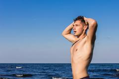 Attractive young man in the sea getting out of water with wet hair Stock Photos