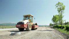 Road roller leveling base for new asphalt.Roadwork.Steamroller flattening gravel Stock Footage