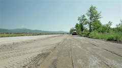 Road roller flattens gravel on the road before paving,roadworks,wide angle view. - stock footage