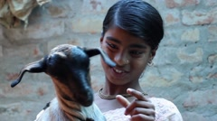 Indian village girl plays and smiles with friendly goat 2 Stock Footage