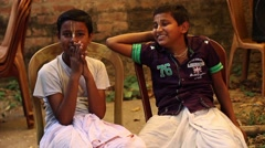 Two Indian village boys have fun, sitting in chairs and joking around with each  - stock footage