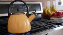 Steam from a yellow tea kettle on stove Stock Footage