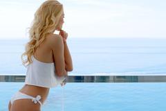 Blond woman wearing white bikini and silky top Stock Photos