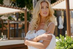 Blond Woman Wearing White Peasant Blouse at Resort - stock photo