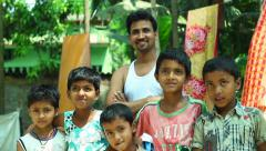 Indian village kids with father smiling and posing for the camera - stock footage