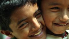 Two Indian village boys smiling and posing for the camera closeup 2 - stock footage