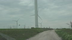view from the car window on the wind turbines on the horizon dirt road - stock footage