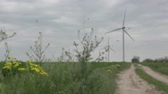Dirt road along side of the grass on horizon of wind turbines twist propellers - stock footage