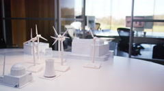 Concept models of buildings and wind turbines on a desk in empty office Stock Footage