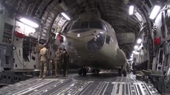 Loading a CH-47F Chinook into a C-17 Globemaster Aircraft Stock Footage