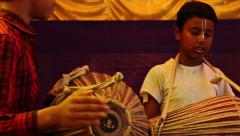 Indian children play traditional tabla drum instruments together panning shot Stock Footage